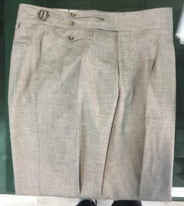 a double pleats trousers in light brown linen fabric with extended waistband, buttoned coin pocket and side buckles