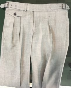 a french double pleats trousers in beige linen fabric with extended waistband, buttoned coin pocket and side buckles