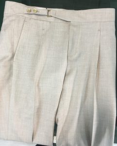 a single pleat trousers in off-white linen fabric with extended waistband, horn buttons and front buckle