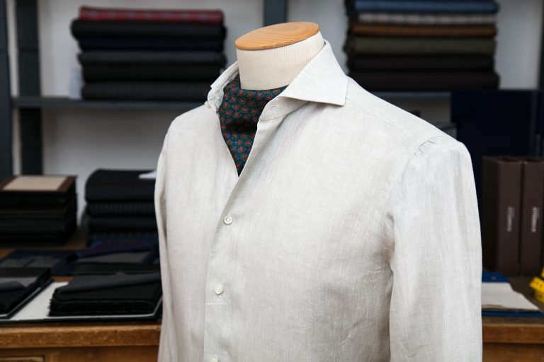 a shirt with a neapolitan shoulder in off-white linen with mother of pearl buttons