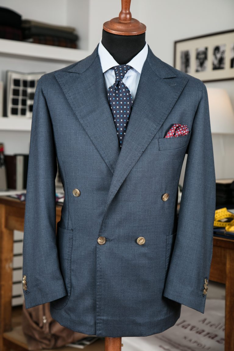 a double-breasted jacket in blue tasmanian wool fabric with horn buttons, peak lapel and patch pockets
