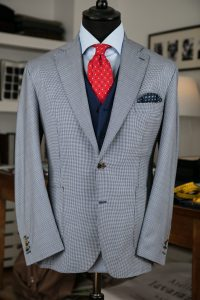 a single-breasted jacket in blue/white houndstooth tasmanian wool fabric with horn buttons, notch lapel and patch pockets
