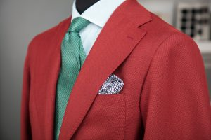 a single-breasted jacket in red opsak wool fabric with horn buttons, notch lapel and patch pockets