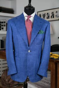 a single-breasted jacket in blue linen/silk fabric with mother-of-pearl buttons, notch lapel and patch pockets