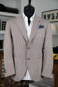 a single-breasted jacket in checked tropical wool fabric with two horn buttons, notch lapel and patch pockets