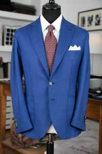 a single-breasted jacket in light blue linen/silk/wool fabric with horn buttons, notch lapel and patch pockets