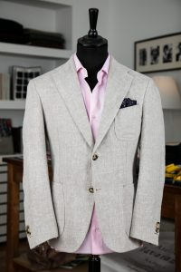 a single-breasted jacket in off-white linen fabric with two horn buttons, notch lapel and patch pockets