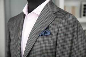 a single-breasted jacket in grey checked tasmanian wool fabric with two horn buttons, notch lapel and patch pockets