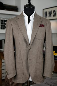 a single-breasted jacket in flannel wool fabric with two horn buttons, notch lapel and patch pockets