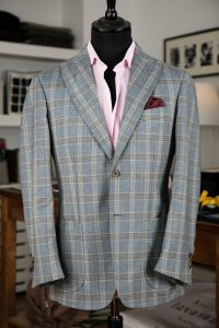 a single-breasted jacket in light blue prince of wales wool fabric with two horn buttons, pick lapel and patch pockets