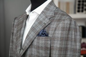 a single-breasted jacket in grey prince of wales wool fabric with three rolled on two horn buttons, notch lapel and patch pockets