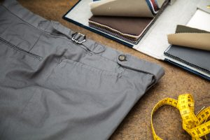 trousers in grey gabardine cotton with extended waistband, horn buttons and side buckles