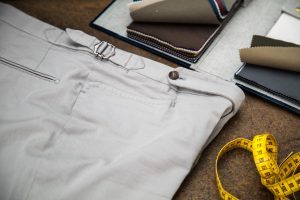 trousers in light grey gabardine cotton with extended waistband, horn buttons and side buckles