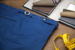 trousers in blue gabardine cotton with extended waistband, horn buttons and side buckles