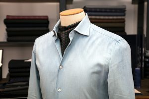 a shirt with a neapolitan shoulder in blue denim cotton with mother of pearl buttons